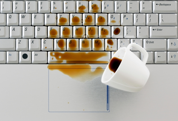 Coffee spilled on keyboard, close up shot. Damaged computer that needs reparation. Data safety and laptop insurance concept.